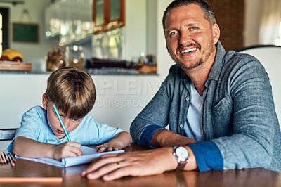 Buy stock photo Shot of a father helping his son with his homework