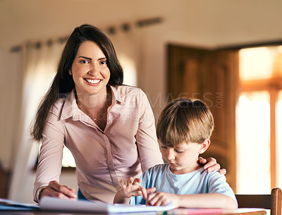 Buy stock photo Shot of a mother helping her son with his homework