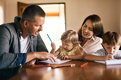 Buy stock photo Shot of a young family of four drawing and getting creative together at home