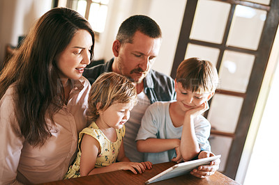 Buy stock photo Shot of a young family of four using a digital tablet together at home