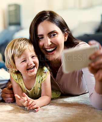 Buy stock photo Shot of a happy mother and her adorable daughter taking selfies together at home
