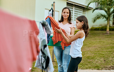 Buy stock photo Shot of a mother and daughter hanging up laundry together outside