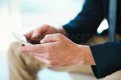 Buy stock photo High angle shot of an unrecognizable businessman sending a text message