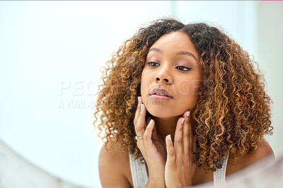Buy stock photo Shot of a confident young woman holding her face while looking at herself in the mirror at home in the bathroom