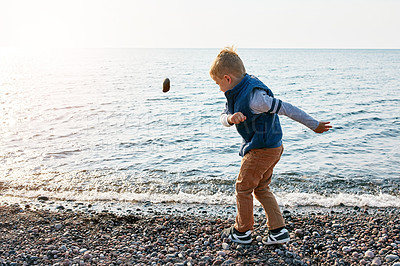 Buy stock photo Shot of a little boy throwing a rock into the lake