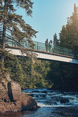 Buy stock photo Shot of a young couple standing on a bridge surrounded by nature