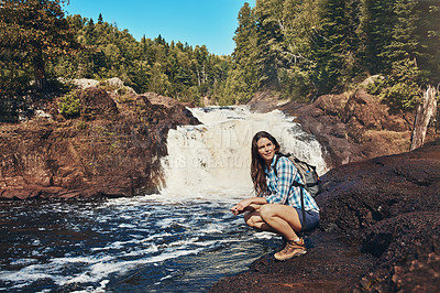 Buy stock photo Shot of an attractive young woman crouching next to a rocky river and waterfall