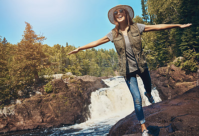 Buy stock photo Shot of a young woman having fun next to a rocky river and waterfall
