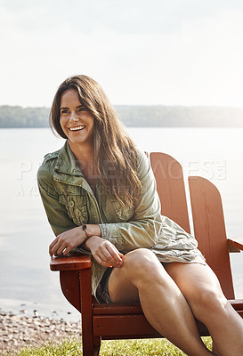 Buy stock photo Shot of an attractive young woman relaxing at the lake