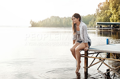 Buy stock photo Shot of an attractive young woman sitting on a pier