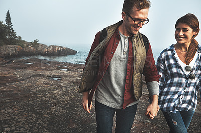 Buy stock photo Shot of a cheerful young couple holding hands and walking together next to the ocean outside during the day