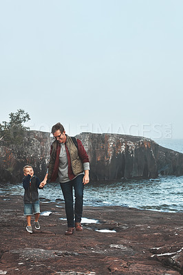 Buy stock photo Shot of a cheerful father and son holding hands while walking next to the ocean outside during the day