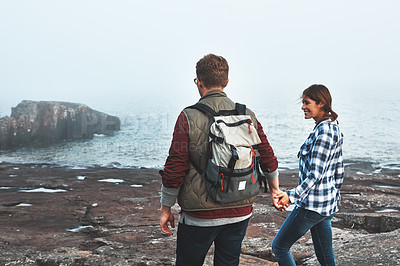Buy stock photo Shot of a happy couple out hiking hand in hand