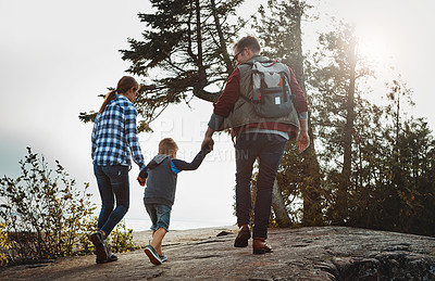 Buy stock photo Rearview shot of a cheerful young family holding hands and walking together up a hill outside during the day