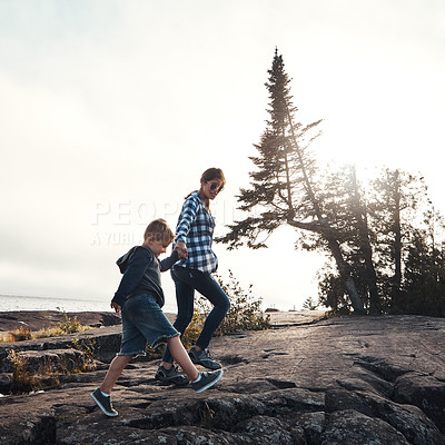 Buy stock photo Shot of a cheerful mother and son holding hands while walking outside in nature during the day