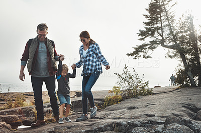 Buy stock photo Shot of a cheerful young family holding hands and walking together down a hill outside during the day