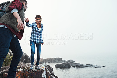 Buy stock photo Shot of a couple crossing over rocks while out exploring nature