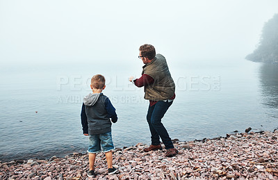 Buy stock photo Rearview shot of a cheerful father and son throwing flat stones into a lake while standing next to the water
