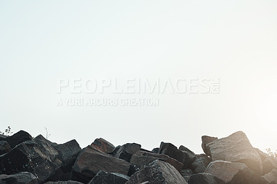 Buy stock photo Shot of a group of sharp rocks next to each with the sun peeking out in the horizon outside during the day