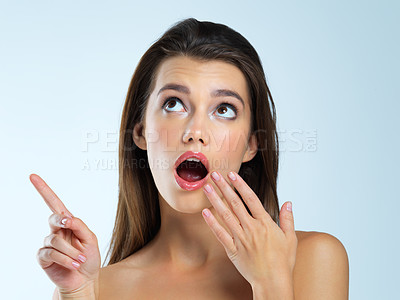 Buy stock photo Studio shot of a beautiful young woman looking shocked against a blue background