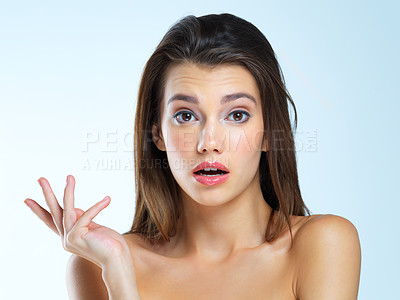 Buy stock photo Studio portrait of a beautiful young woman looking confused against a blue background