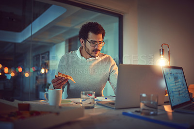 Buy stock photo Shot of a young designer eating pizza while working late in an office