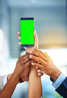 Buy stock photo Cropped shot of a group of businesspeople holding a mobile phone with a green screen in a modern office