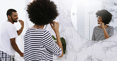 Buy stock photo Rearview shot of a cheerful young couple brushing their teeth in bathroom together at home