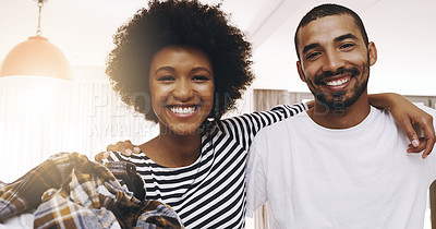 Buy stock photo Portrait of a cheerful young couple standing huddled together with a bundle of washing at home during the day