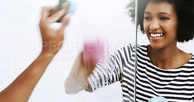 Buy stock photo Shot of a cheerful young woman washing a glass shower door with a sponge in the bathroom at home