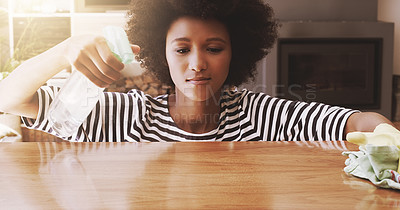 Buy stock photo Shot of a focused young woman cleaning the surface of a table with cleaning equipment at home during the day