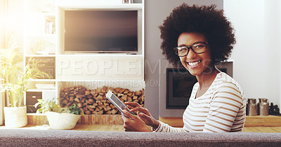 Buy stock photo Portrait of a cheerful young woman wearing glasses while browsing on a digital tablet and seated next to a couch at home