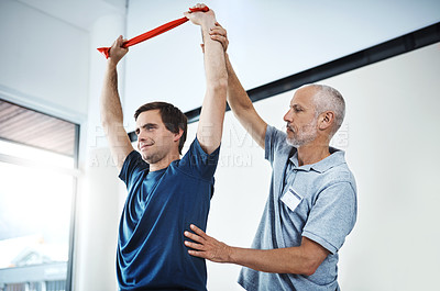 Buy stock photo Shot of a physiotherapist helping a patient stretch with resistance bands