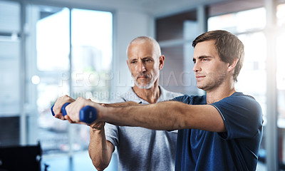 Buy stock photo Shot of a physiotherapist helping a patient work through his recovery with weights