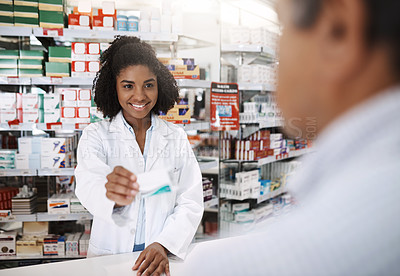 Buy stock photo Cropped shot of an attractive young female pharmacist helping a customer in a pharmacy