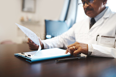 Buy stock photo Shot of a mature doctor going through paperwork in his office