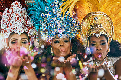 Buy stock photo Cropped shot of beautiful samba dancers blowing confetti from their hands in a carnival