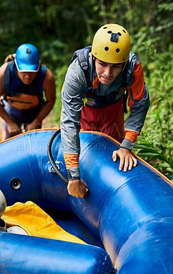 Buy stock photo Shot of a determined young man wearing protective gear while dragging a rubber boat outside during the day