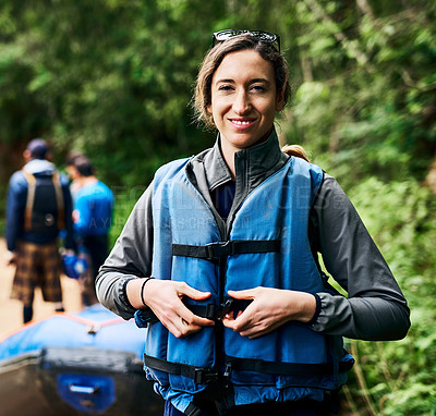 Buy stock photo Portrait of a cheerful young woman putting on a life jacket to go river rafting outside during the day