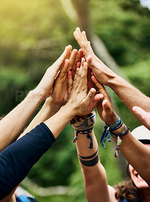 Buy stock photo Shot of a group of unrecognizable people's hands raised in the air to form a huddle together outside during the day