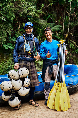 Buy stock photo Portrait of two cheerful men standing together next to a rubber boat while holding river rafting equipment outside during the day