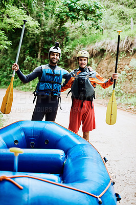 Buy stock photo Portrait of two cheerful young men wearing protective gear while each holding a paddle to go river rafting