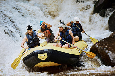 Buy stock photo Shot of a group of determined young men on a rubber boat busy paddling on strong river rapids outside during the day