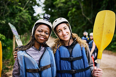 Buy stock photo Portrait of two cheerful young women wearing protective gear while holding a rowing paddle outside during the day