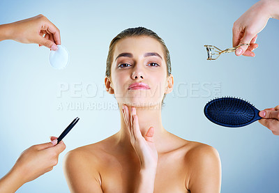 Buy stock photo Studio portrait of a beautiful young woman with an assortment of beauty tools around her against a blue background
