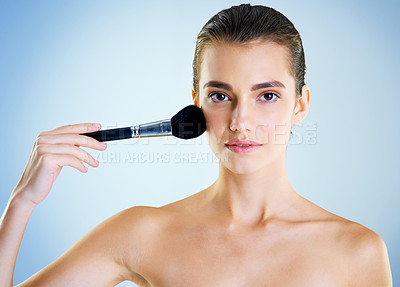 Buy stock photo Studio portrait of a beautiful young woman applying makeup with a brush against a blue background