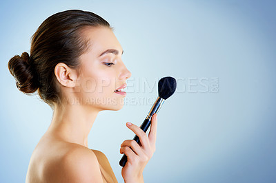 Buy stock photo Studio shot of a beautiful young woman holding a makeup brush against a blue background