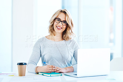 Buy stock photo Portrait of an attractive young businesswoman working on a laptop in an office