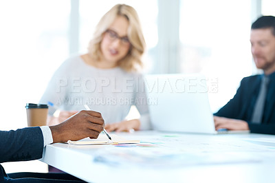 Buy stock photo Closeup shot of an unrecognizable businessman writing notes while in a meeting with his colleagues