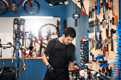 Buy stock photo Shot of a man working in a bicycle repair shop